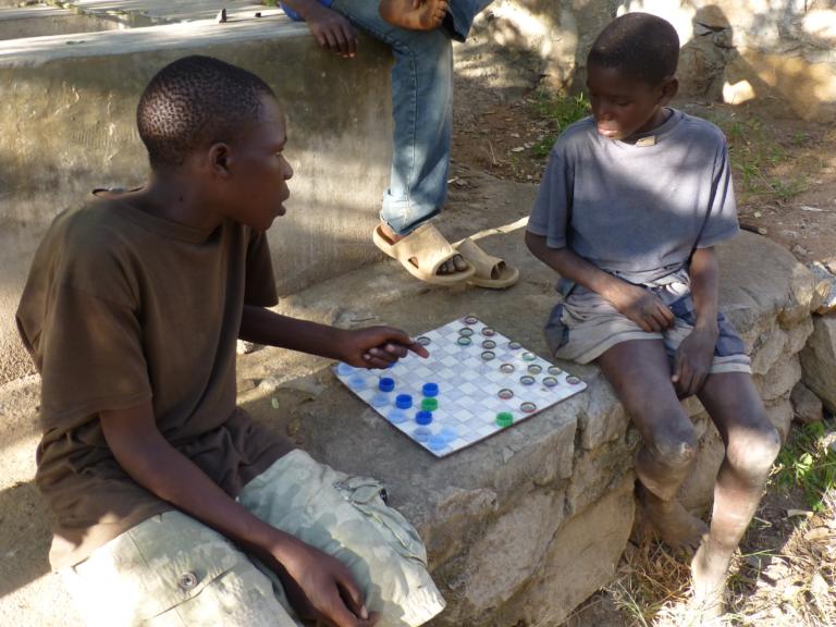 In hun vrije tijd spelen de jongens graag spelletjes. Dit dambord hebben ze zelf gemaakt van een oud stuk karton en flessendopjes.